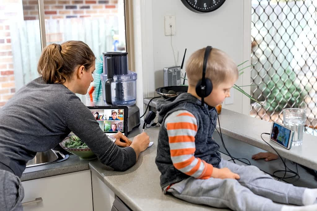 Woman and child in the kitchen using technology