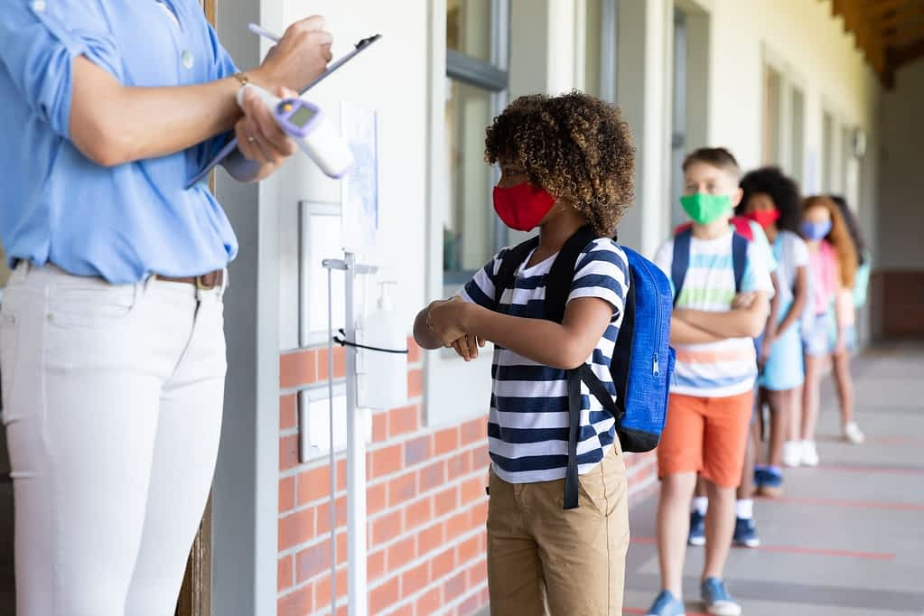 Boy wearing face mask sanitizing her hands at school