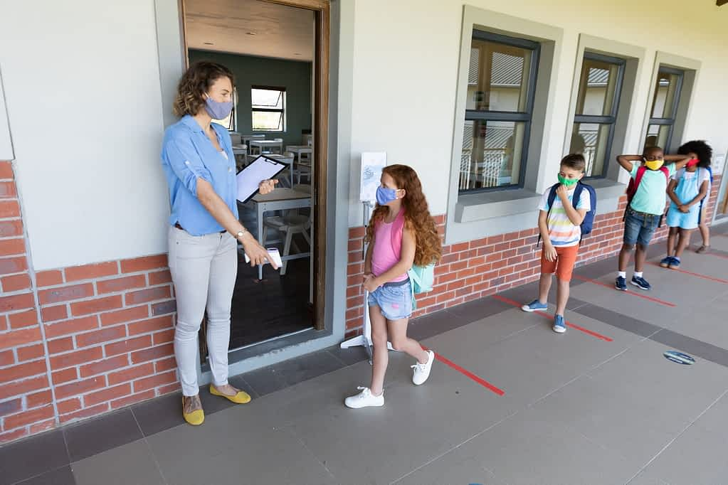 Female teacher wearing face mask pointing girl to stand on the marker